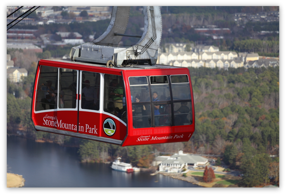 Stone Mountain Park, Dec 03, 2012 - The red Summit Skyride/Skylift car ascends to the top of Stone Mountain while the passenger in the front eyes me taking her photo